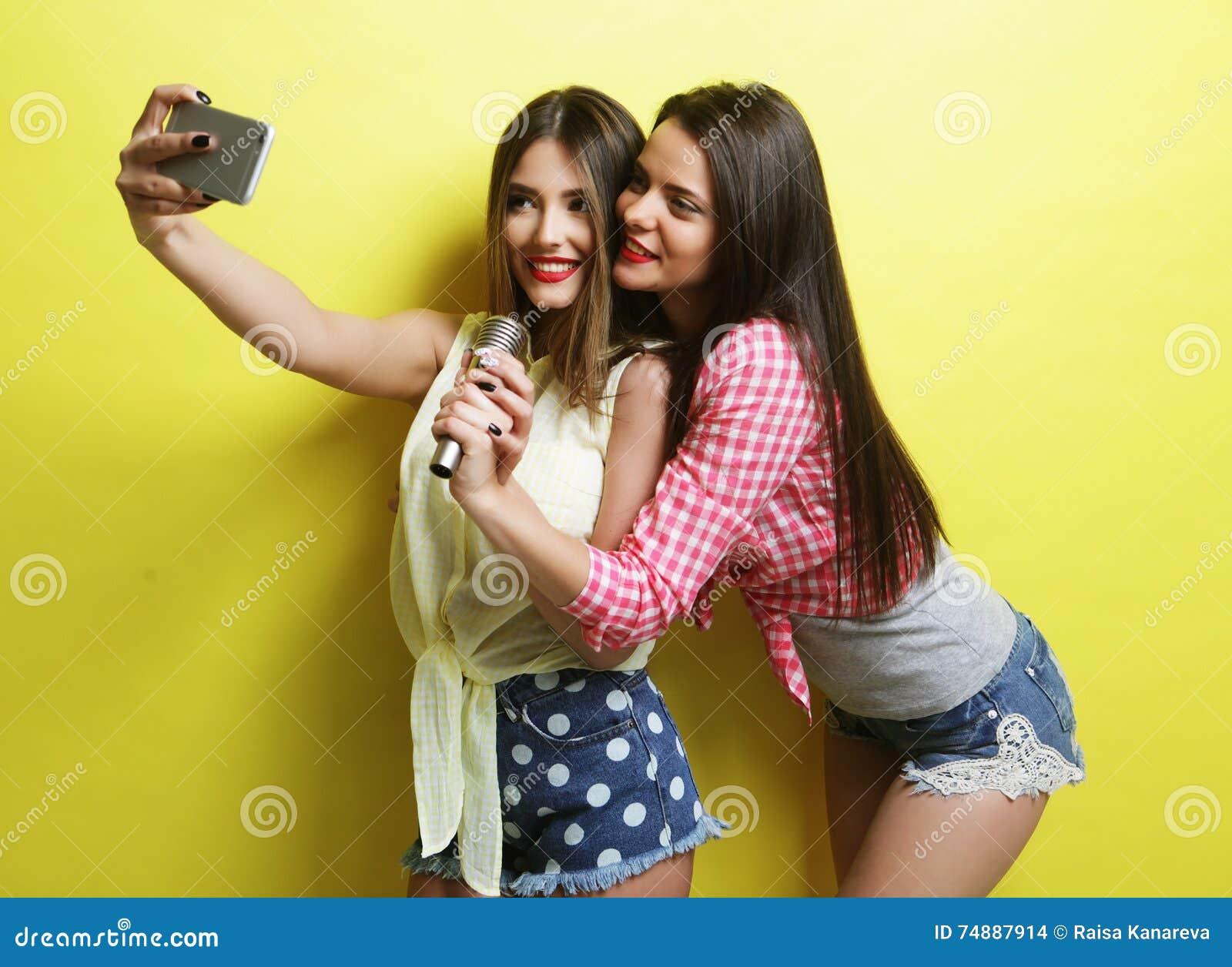 Δύο κορίτσια ομορφιάς hipster με ένα μικρόφωνο παίρνουν το selfi