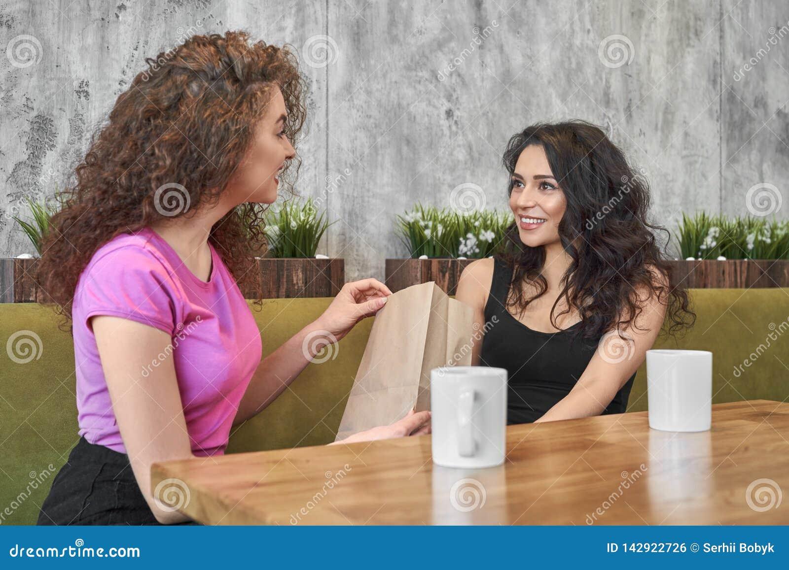 Δύο κορίτσια που κάθονται στον καφέ, που δίνει το παρόν