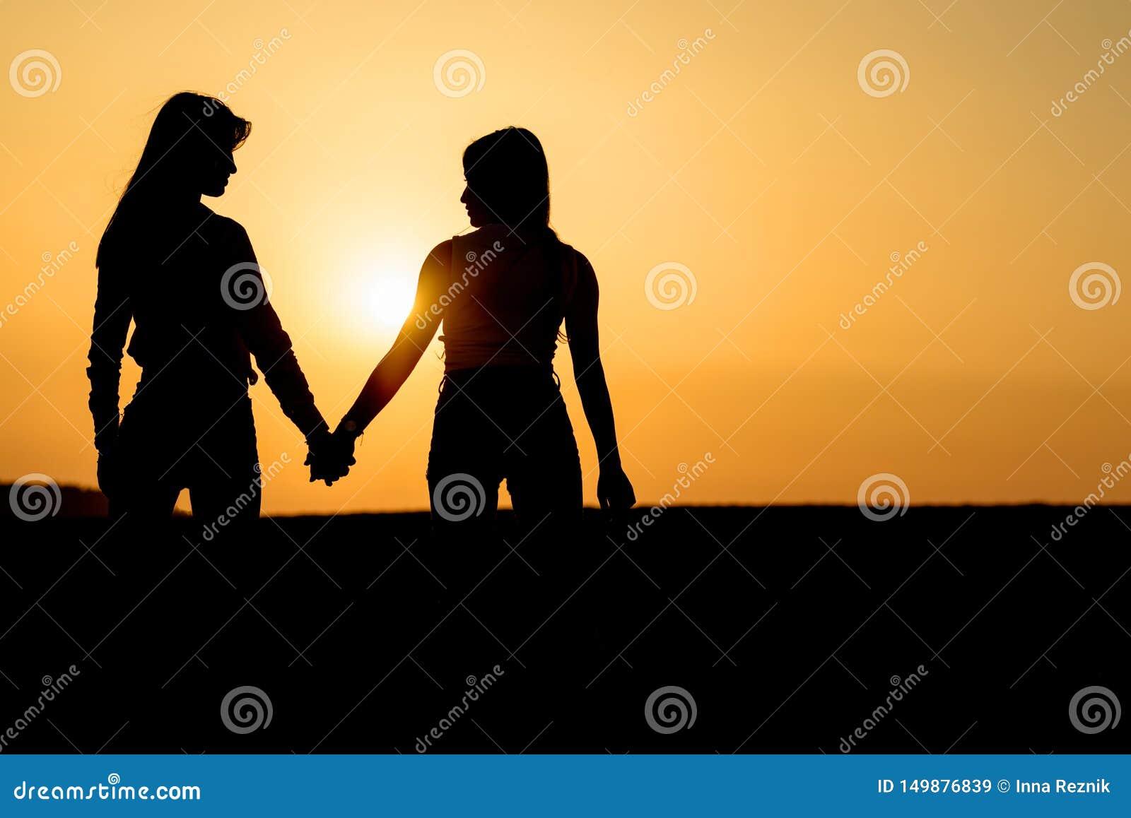Δύο κορίτσια που κρατούν το ένα το άλλο δίνουν Οι κυρίες συνδέουν στην παραλία