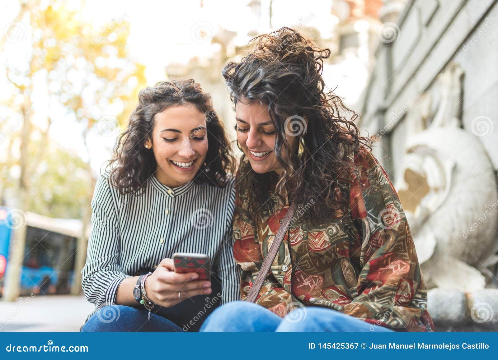 Δύο κορίτσια φίλων που χρησιμοποιούν το κινητό τηλέφωνο υπαίθρια