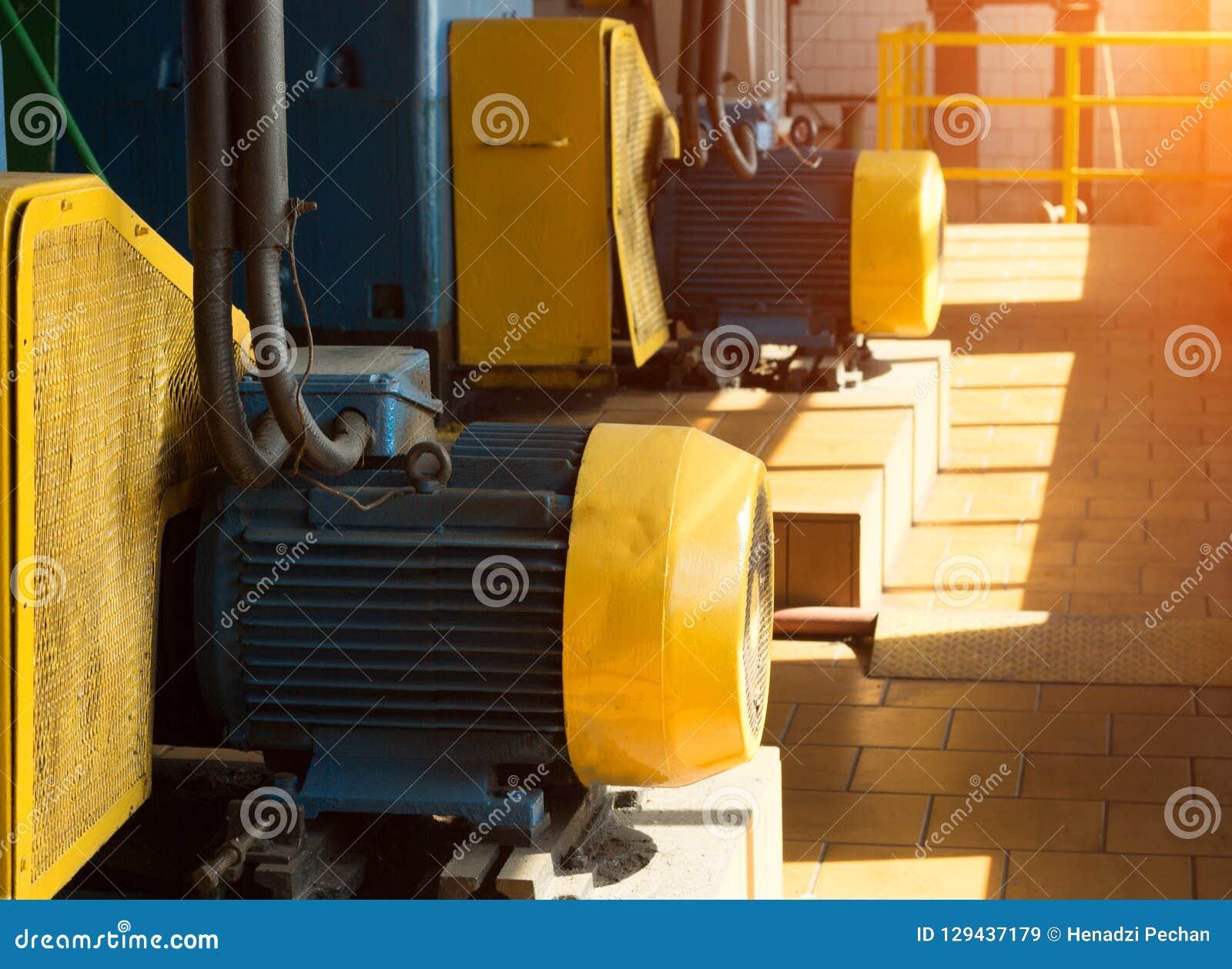 Δύο μεγάλοι ηλεκτρικοί κινητήρες στο εργαστήριο παραγωγής, στα πλαίσια του φωτός του ήλιου, ηλεκτρικός κινητήρας
