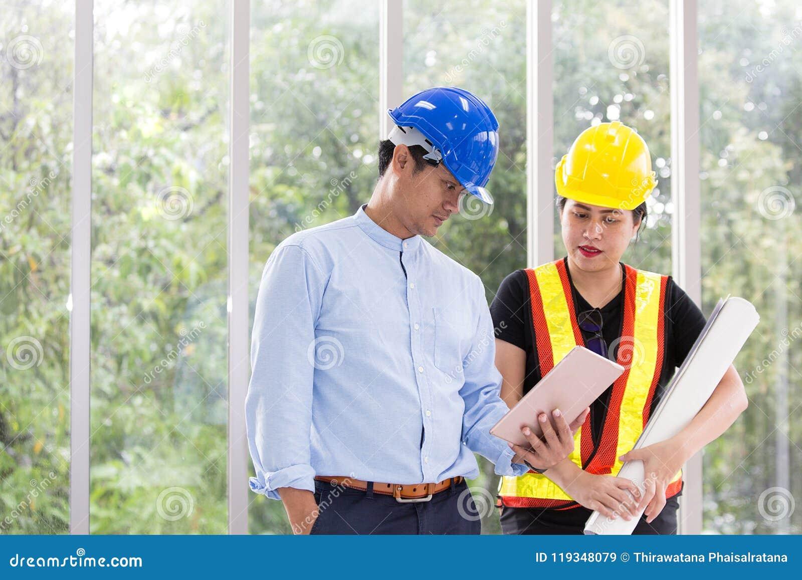 Δύο μηχανικοί που απασχολούνται στην αίθουσα συνεδριάσεων με μια ταμπλέτα Δύο εργαζόμενοι προσέχουν το σχέδιο κατασκευής στο γραφ