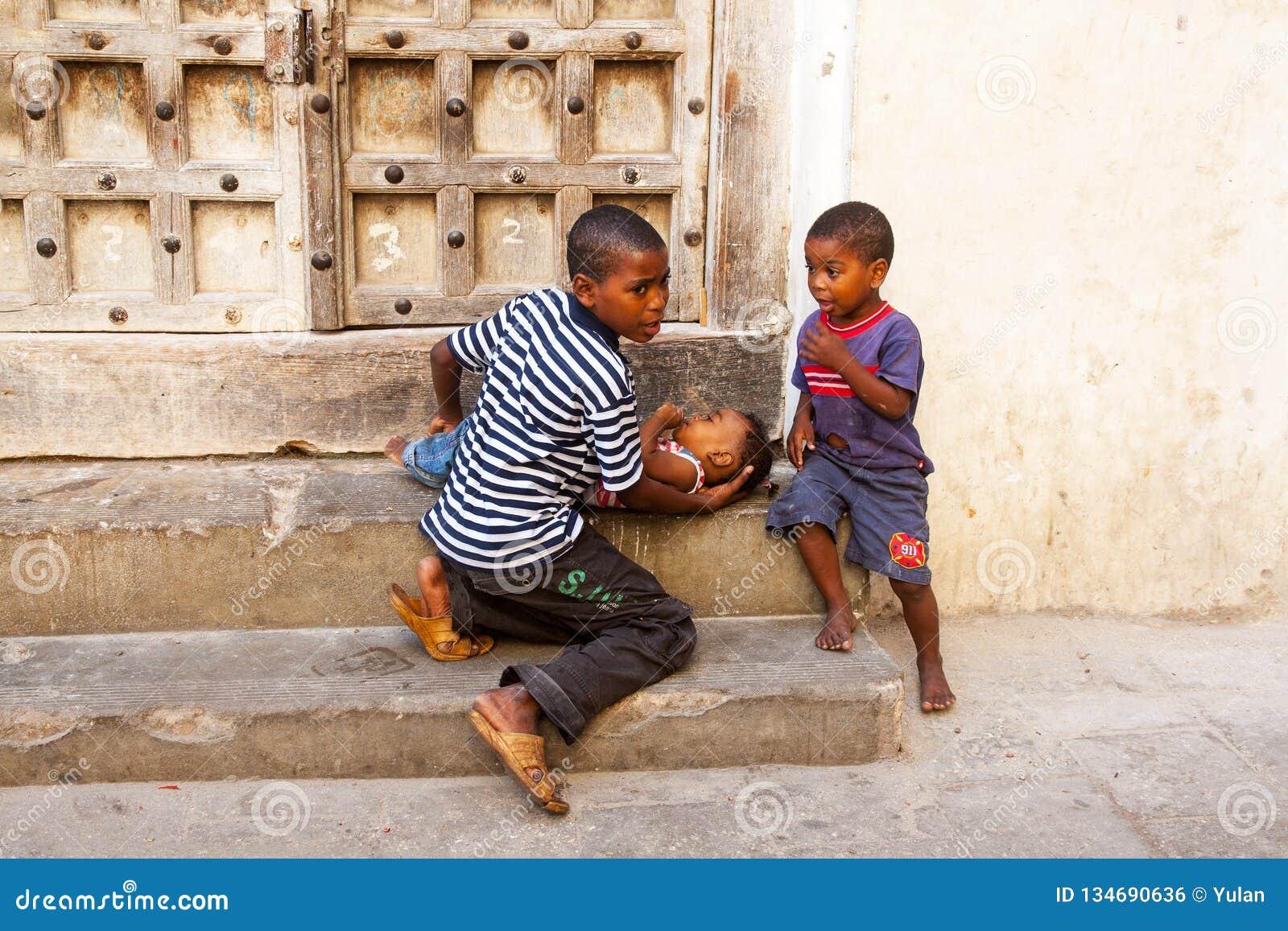 Δύο μικρά αφρικανικά αγόρια φροντίζουν το μικρότερο αδερφό τους
