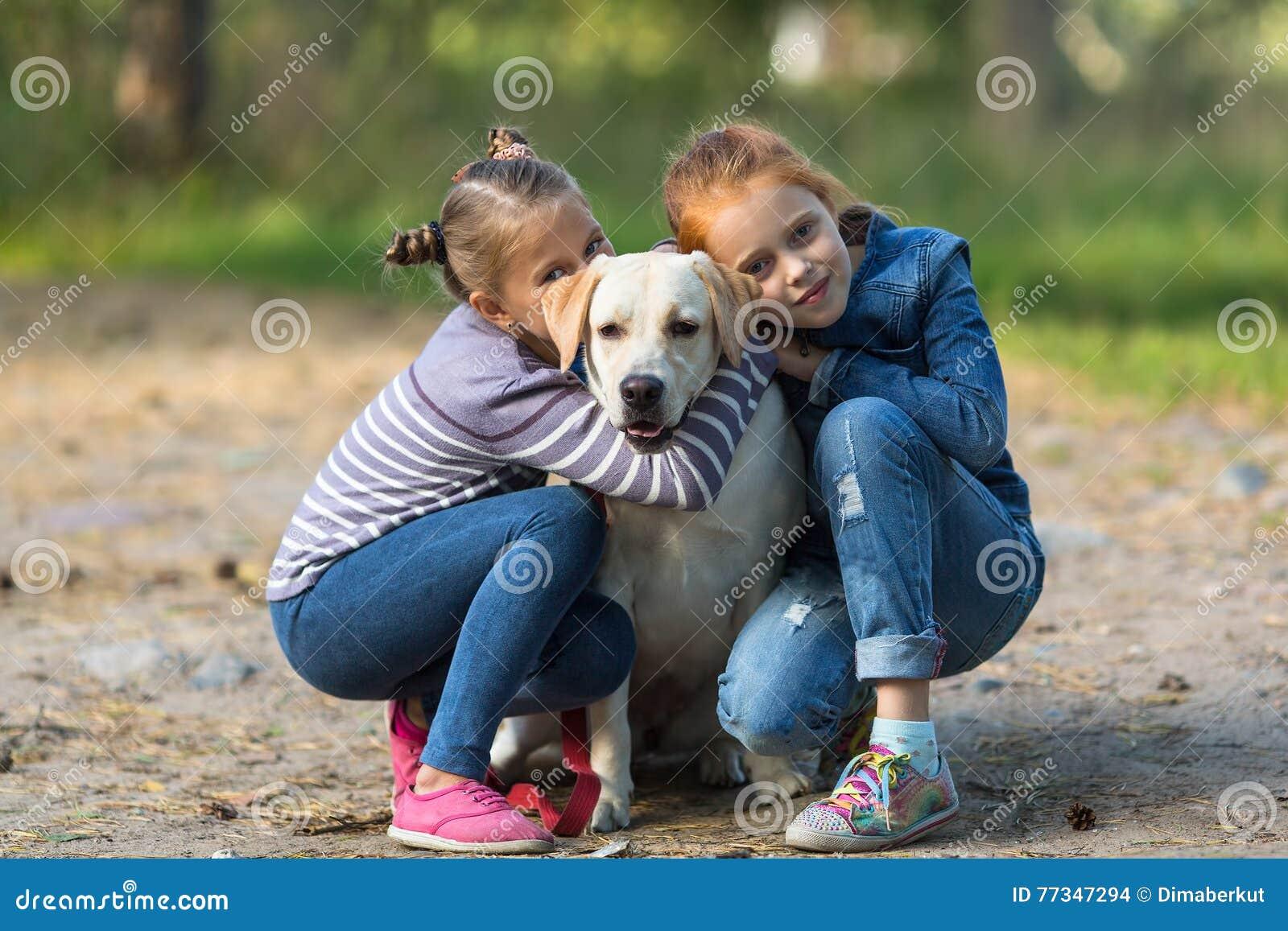 Δύο μικρά κορίτσια με το σκυλί υπαίθρια παιχνίδια