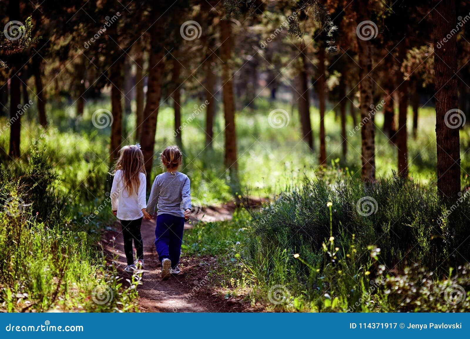 Δύο μικρές αδελφές που περπατούν και που παίζουν στο δρόμο στην επαρχία σε ένα θερμό θερινό ηλιοβασίλεμα χαριτωμένα κορίτσια λίγα