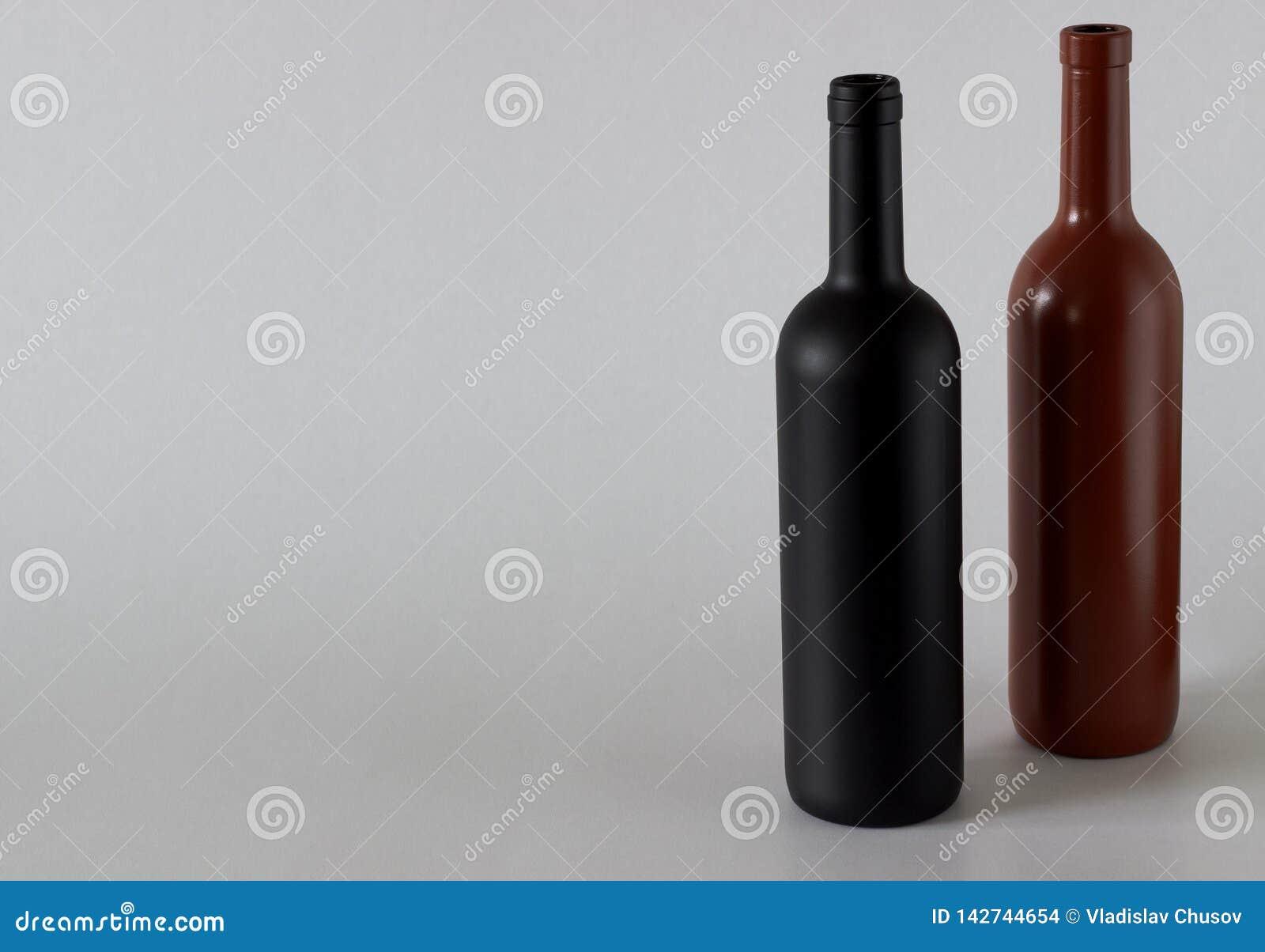 Δύο μπουκάλια του κρασιού μαύρος και κόκκινος σε ένα άσπρο υπόβαθρο