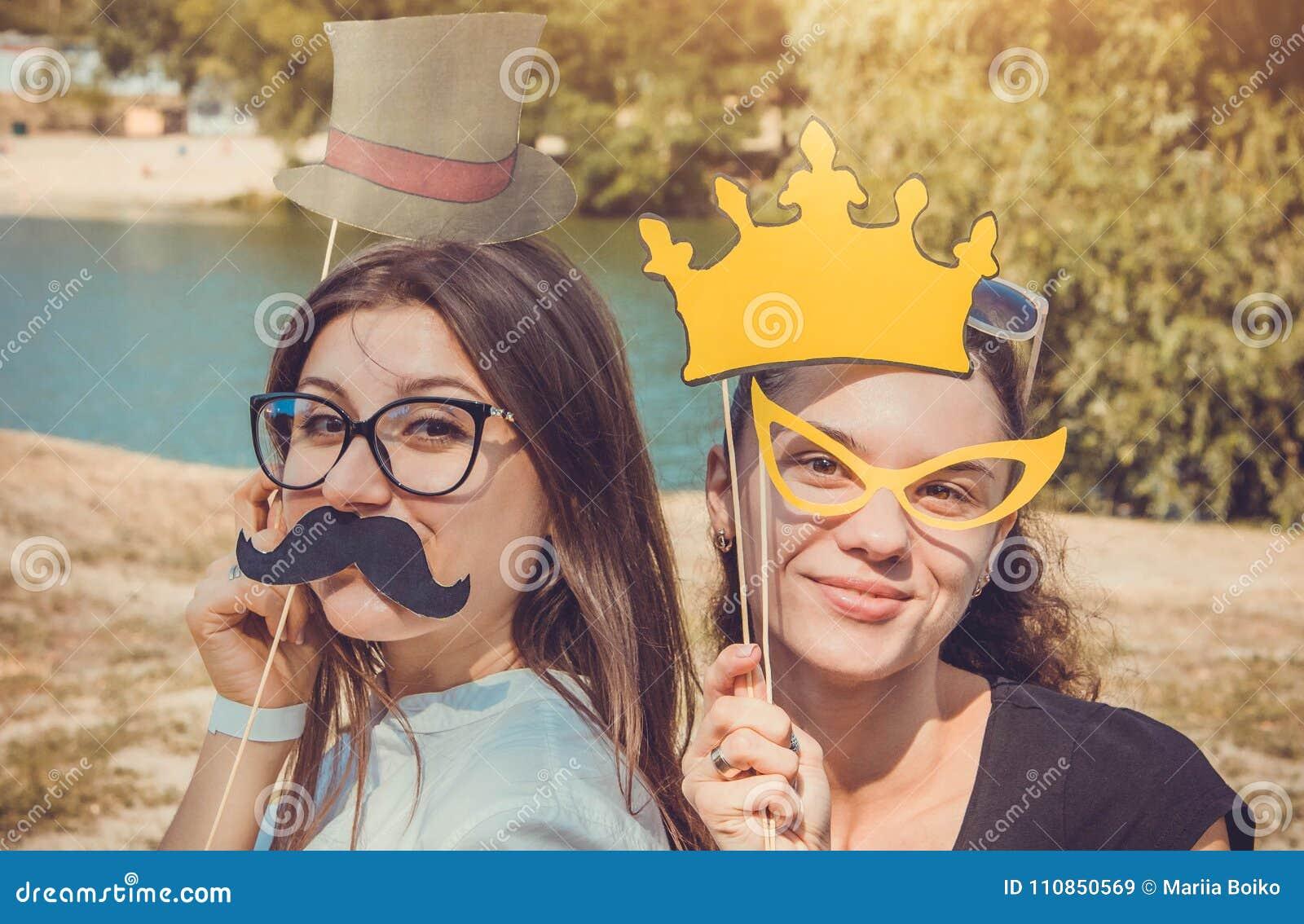 Δύο νέες γυναίκες που θέτουν χρησιμοποιώντας τα στηρίγματα θαλάμων φωτογραφιών