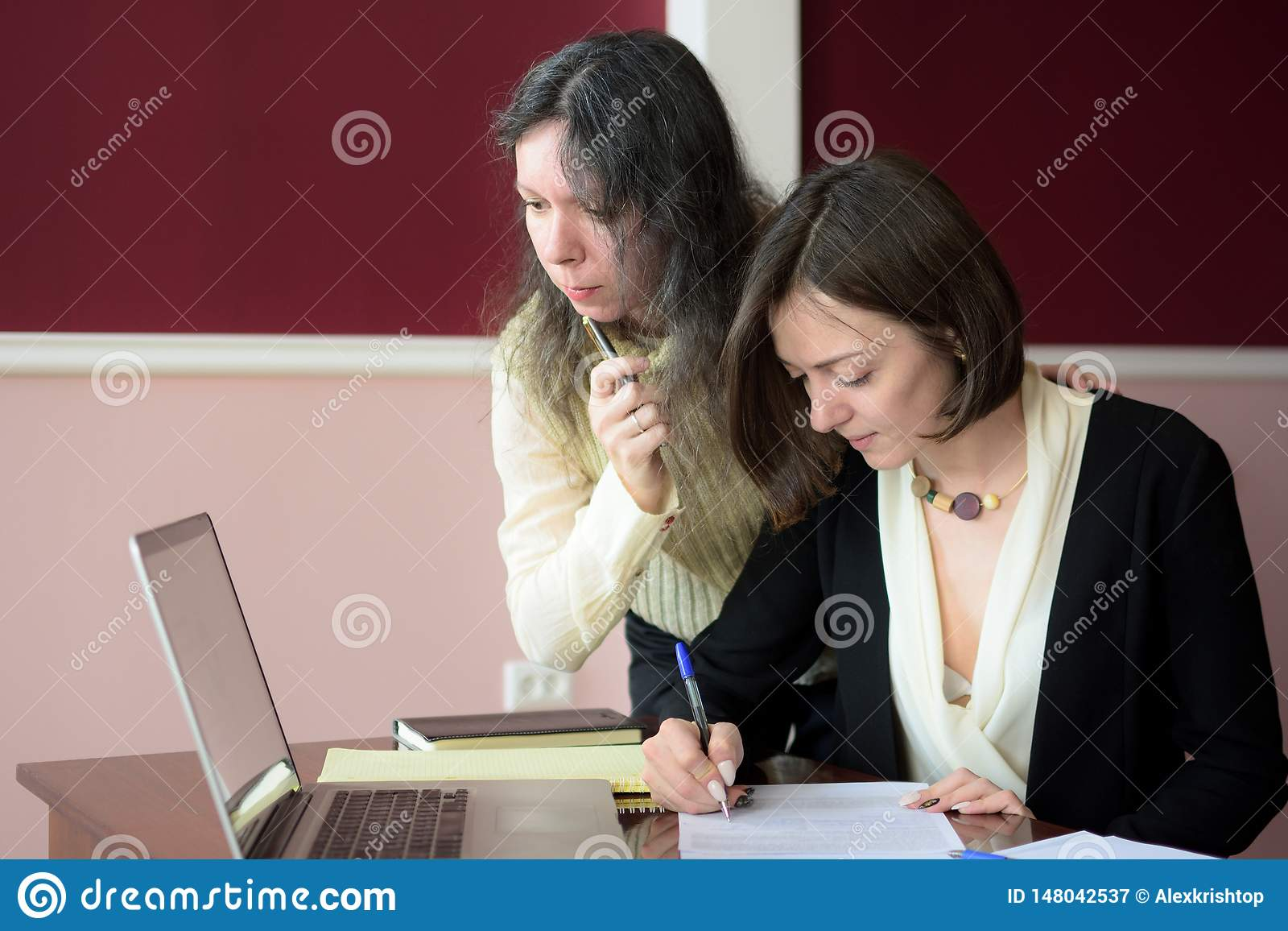 Δύο νεολαίες έντυσαν επιδέξια τη συμπλήρωση γυναικών διαμορφώνουν σε ένα εκλεκτής ποιότητας γραφείο γραφείων μπροστά από ένα lap-