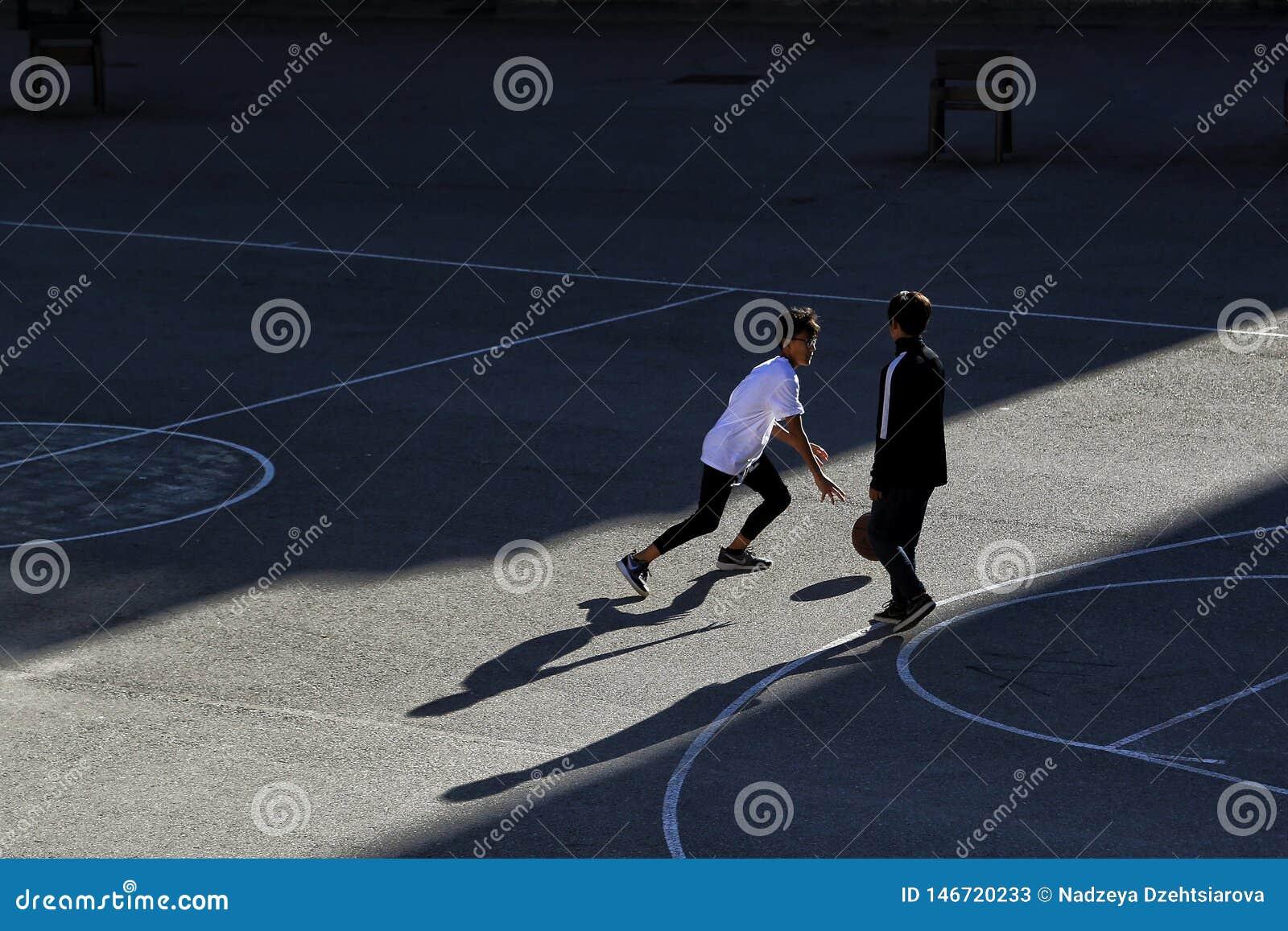 Δύο παιδιά παίζουν την καλαθοσφαίριση σε έναν αθλητικό τομέα οδών