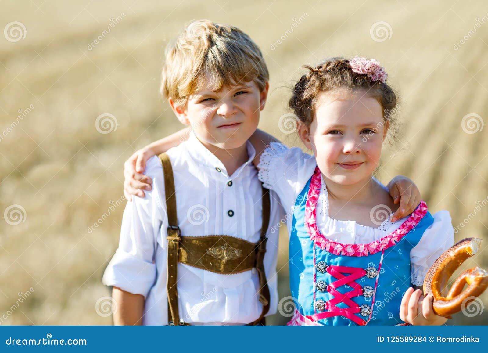 Δύο παιδιά στα παραδοσιακά βαυαρικά κοστούμια στον τομέα σίτου Γερμανικά παιδιά που τρώνε το ψωμί και pretzel κατά τη διάρκεια Ok
