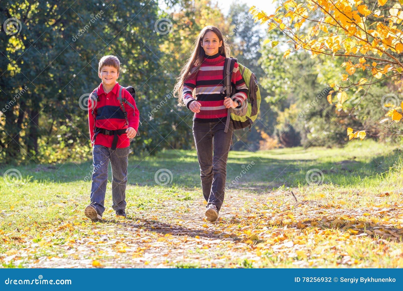 Δύο παιδιά που περπατούν στο δάσος φθινοπώρου με τα σακίδια πλάτης