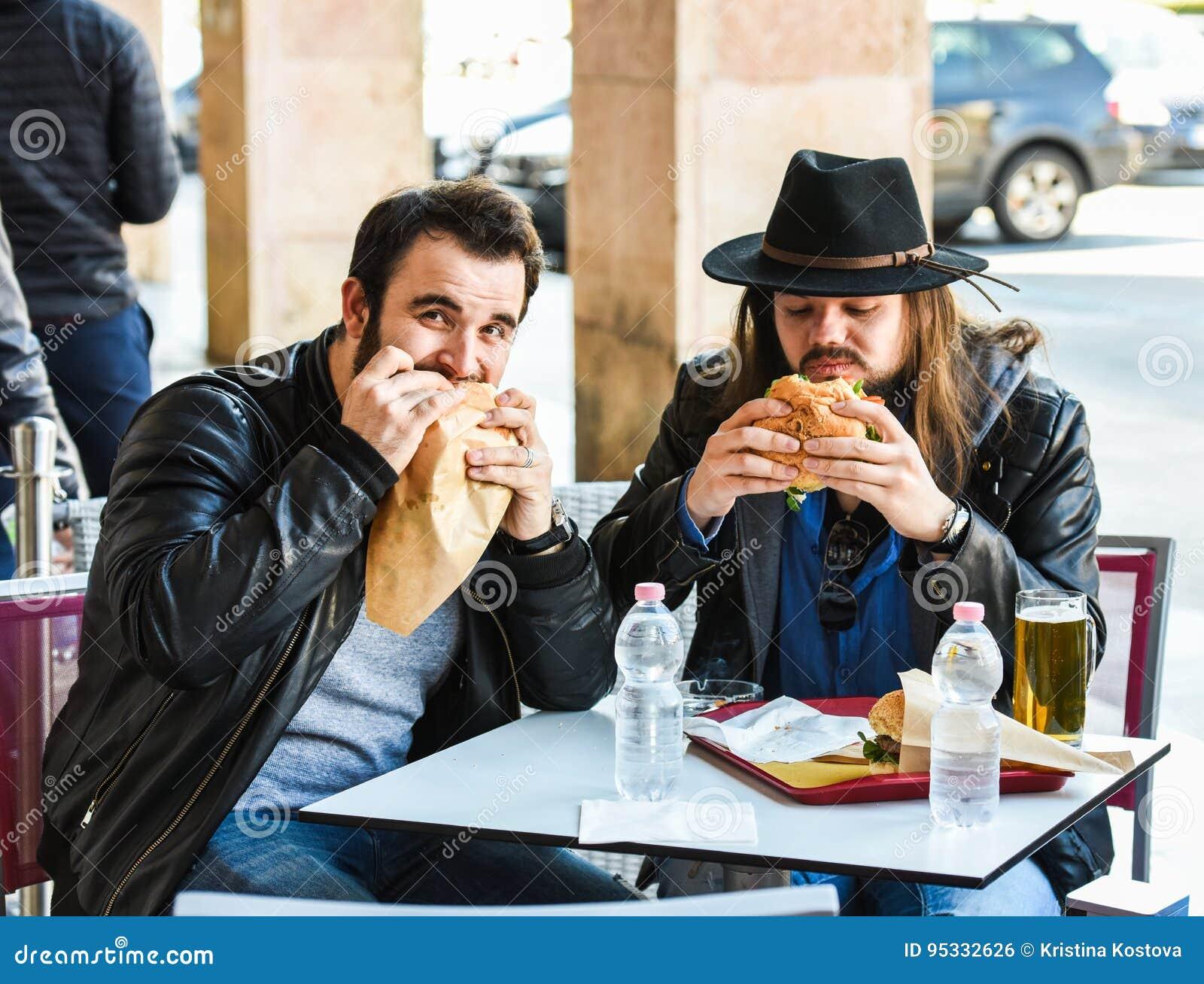 Δύο πεινασμένοι φίλοι/τουρίστες τρώνε τα χάμπουργκερ