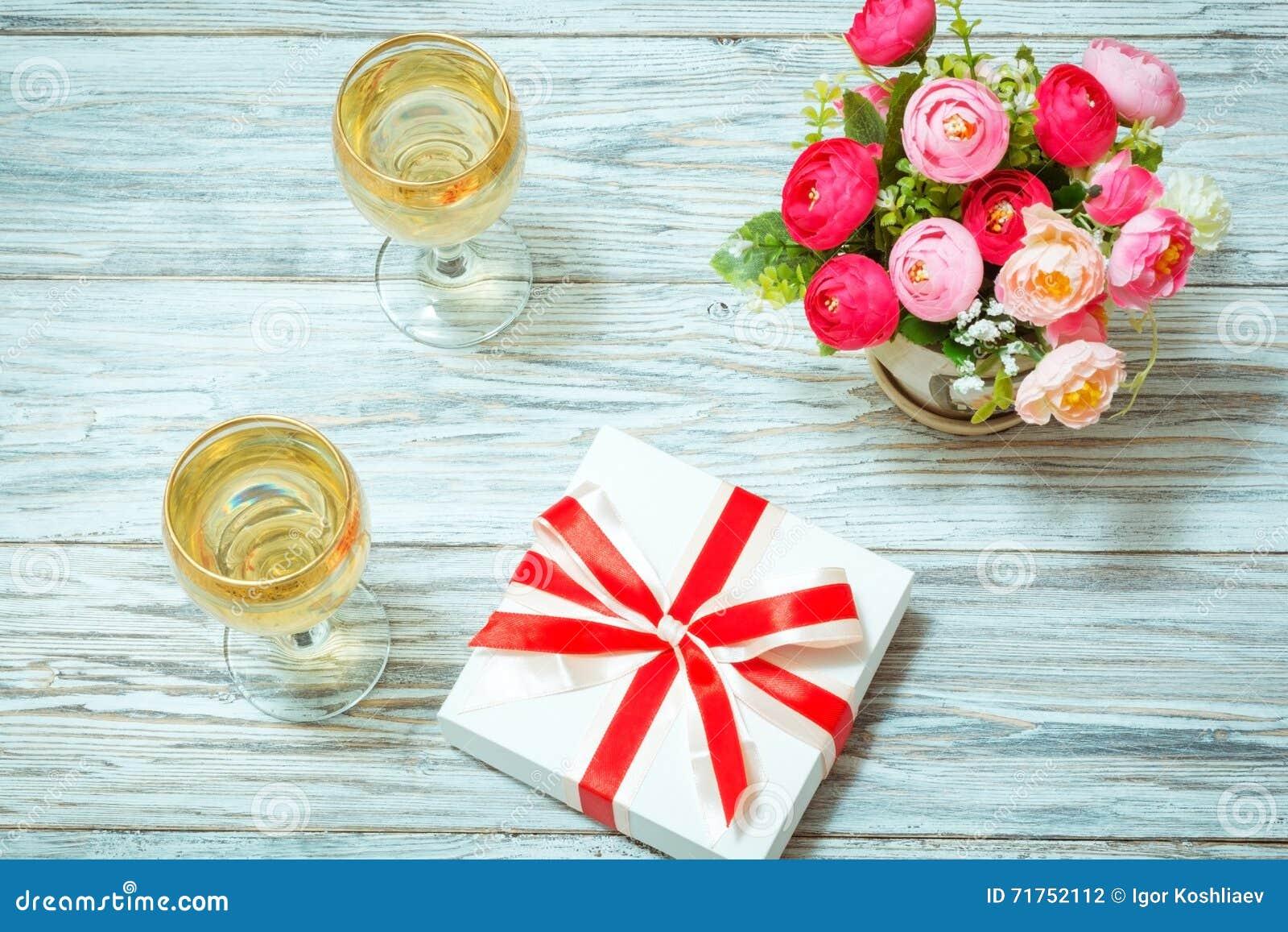 Δύο ποτήρια του άσπρου κρασιού, των λουλουδιών και ενός δώρου