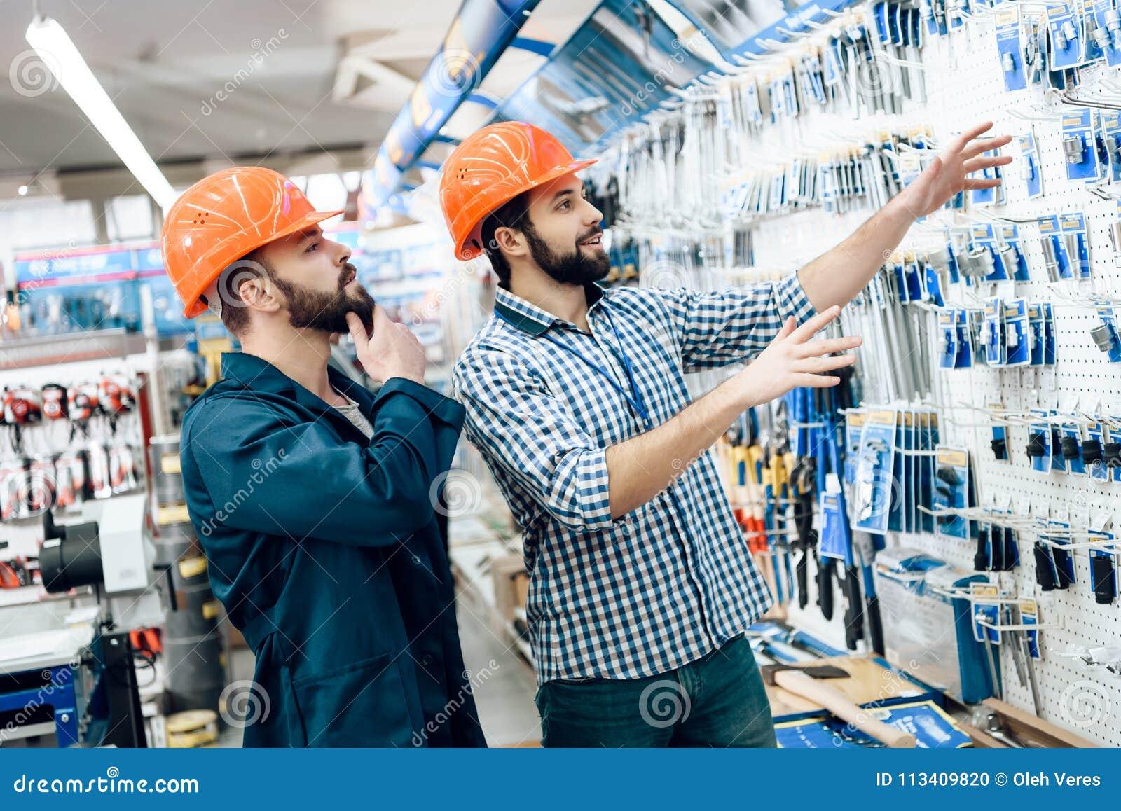 Δύο πωλητές ελέγχουν την επιλογή εξοπλισμού στο κατάστημα εργαλείων δύναμης
