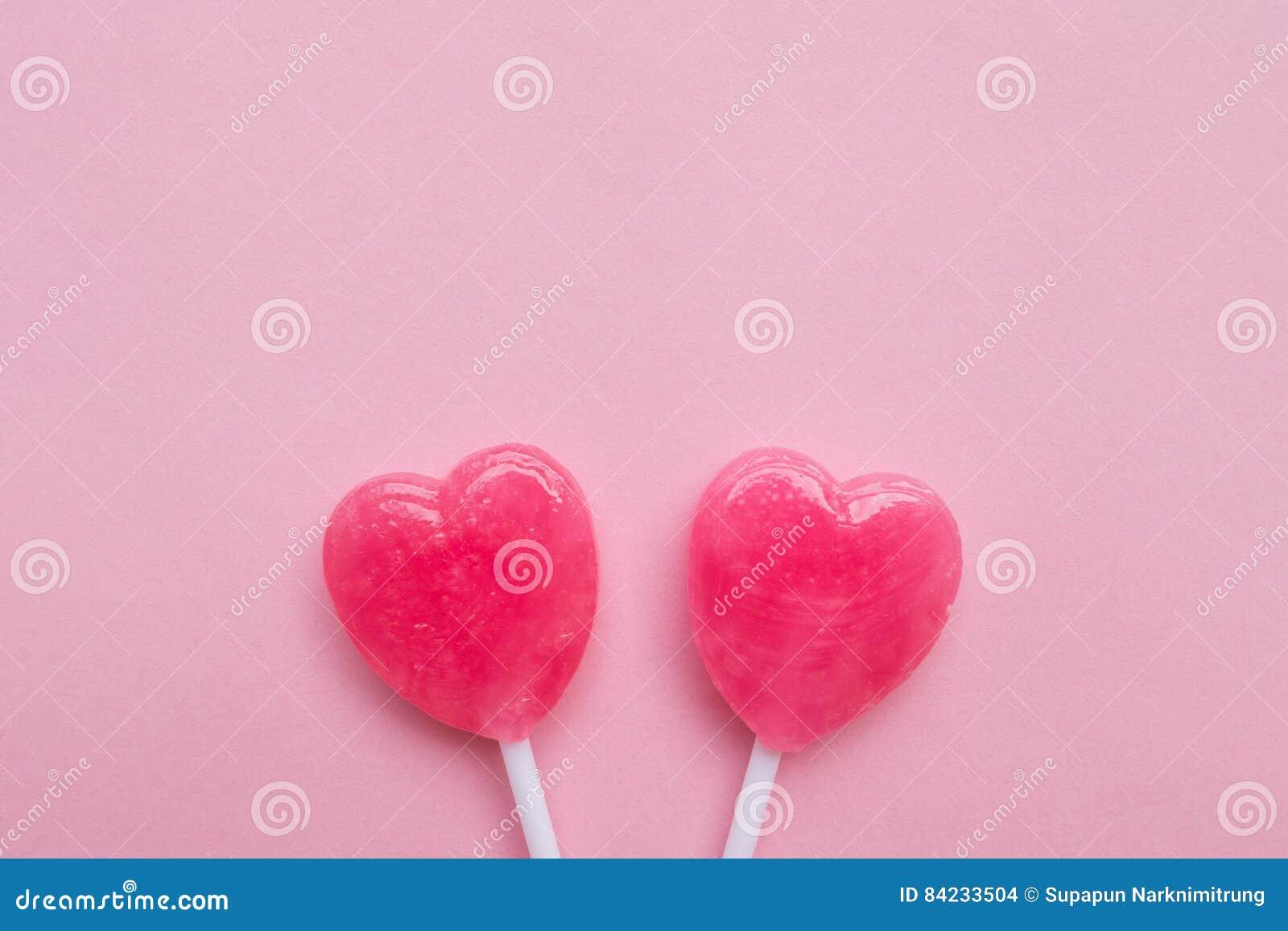 Δύο ρόδινη καραμέλα μορφής καρδιών ημέρας βαλεντίνων ` s lollipop στο κενό ρόδινο υπόβαθρο εγγράφου hipster ελάχιστη έννοια αγάπη