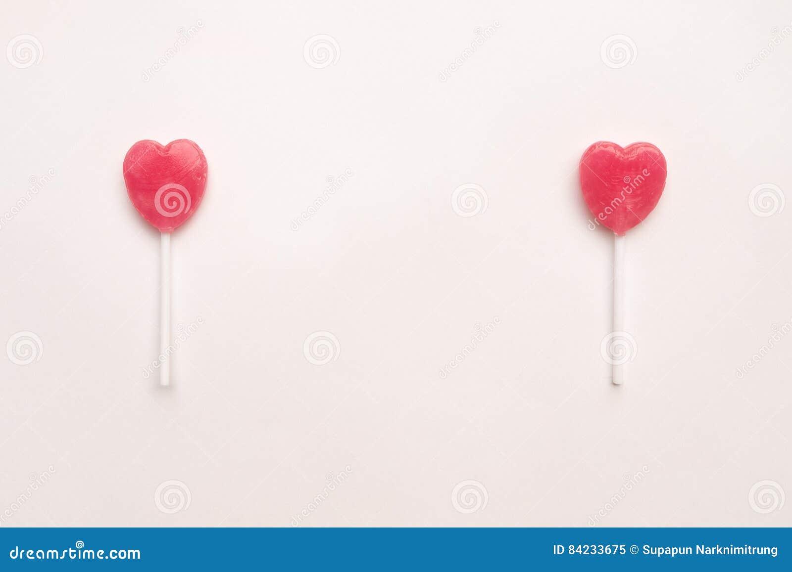 Δύο ρόδινη καραμέλα μορφής καρδιών ημέρας βαλεντίνων ` s lollipop στο κενό υπόβαθρο της Λευκής Βίβλου hipster ελάχιστη έννοια αγά