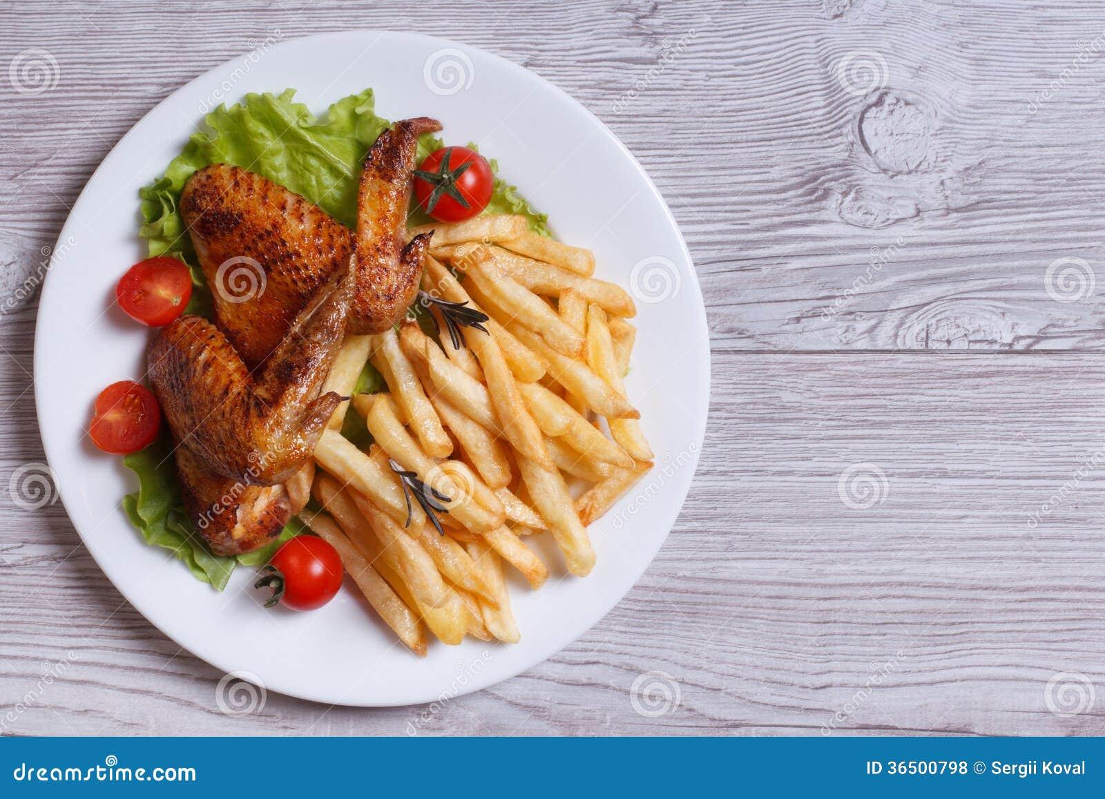 Δύο τηγανισμένα φτερά κοτόπουλου, τηγανιτές πατάτες. τοπ άποψη