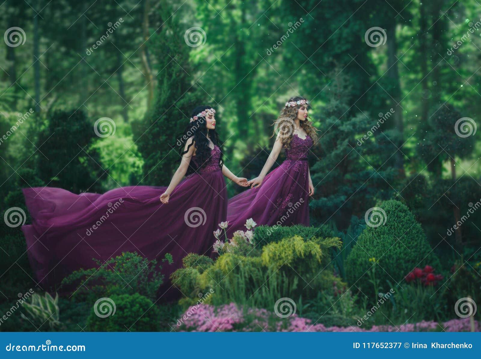 Δύο φίλες, ένας ξανθός και ένα brunette, κρατούν τα χέρια Ανθίζοντας κήπος υποβάθρου Οι πριγκήπισσες είναι ντυμένες στο πολυτελές