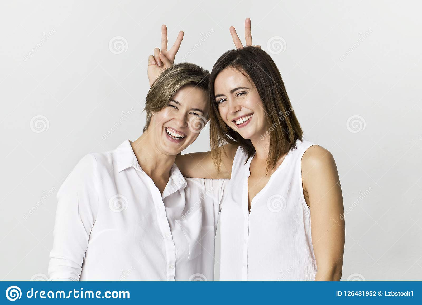 Δύο φίλες που έχουν τη διασκέδαση στο υπόβαθρο στούντιο Οδοντωτό πορτρέτο δύο νέο γυναικών χαμόγελου