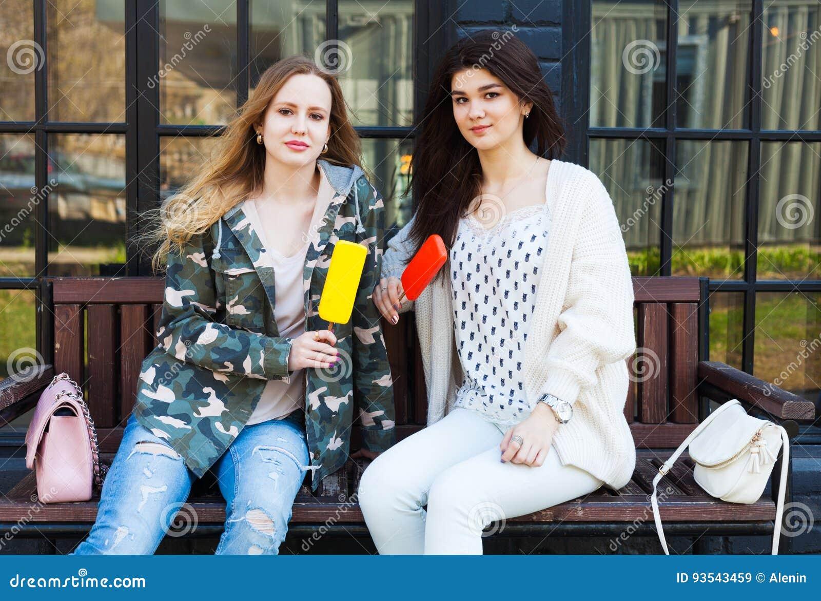Δύο φίλες κοριτσιών που ντύνονται στο υπόλοιπο εξαρτήσεων μόδας, τρώνε το παγωτό eskimo