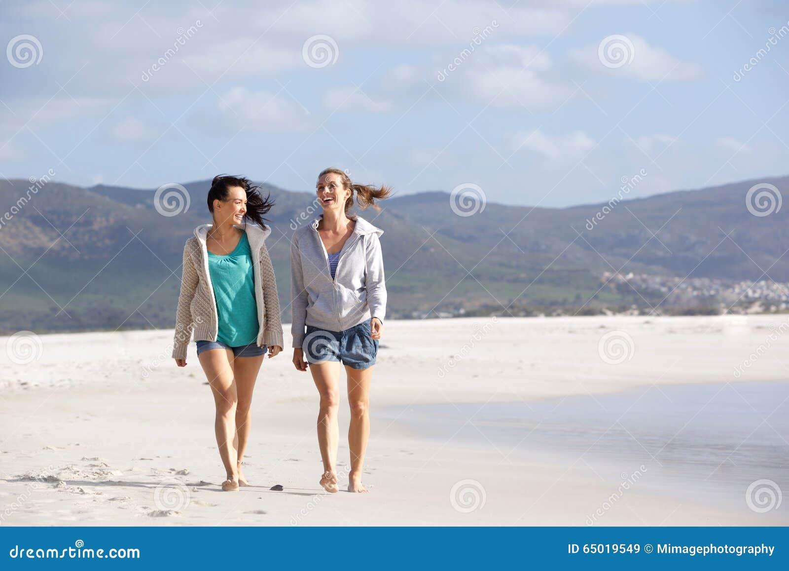 Δύο φίλες που περπατούν και που μιλούν στην παραλία