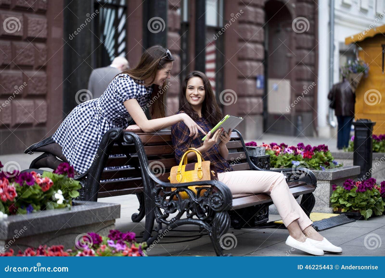 Δύο φίλοι κοριτσιών που κάθονται σε έναν πάγκο στο πόλης κέντρο