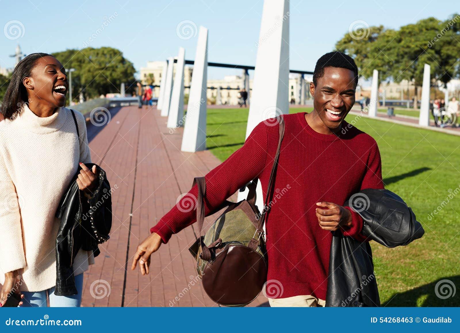 Δύο φίλοι κολλεγίων που γελούν έχοντας τον καλό χρόνο