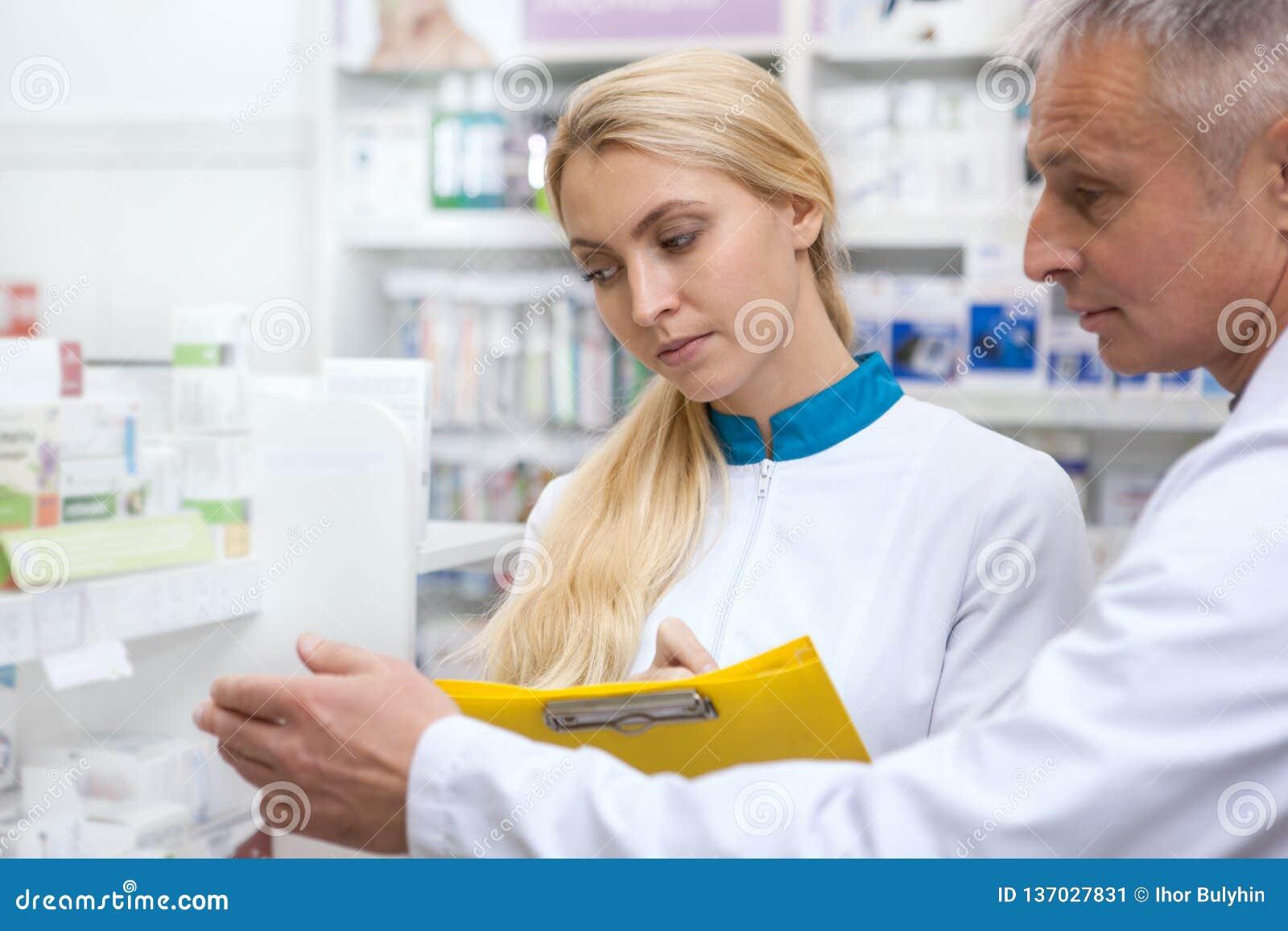 Δύο φαρμακοποιοί που εργάζονται στο φαρμακείο από κοινού