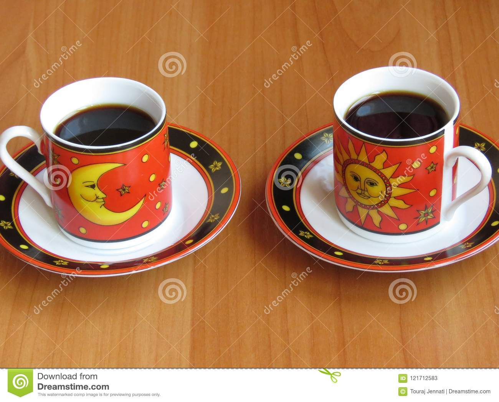 Δύο φλυτζάνια του σκοτεινού καφέ στο κόκκινο με τα στοιχεία φεγγαριών και ήλιων