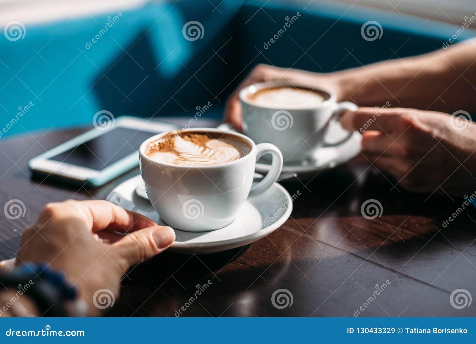 Δύο φλυτζάνια του cappuccino με την τέχνη latte στον ξύλινο πίνακα στα χέρια του άνδρα και της γυναίκας