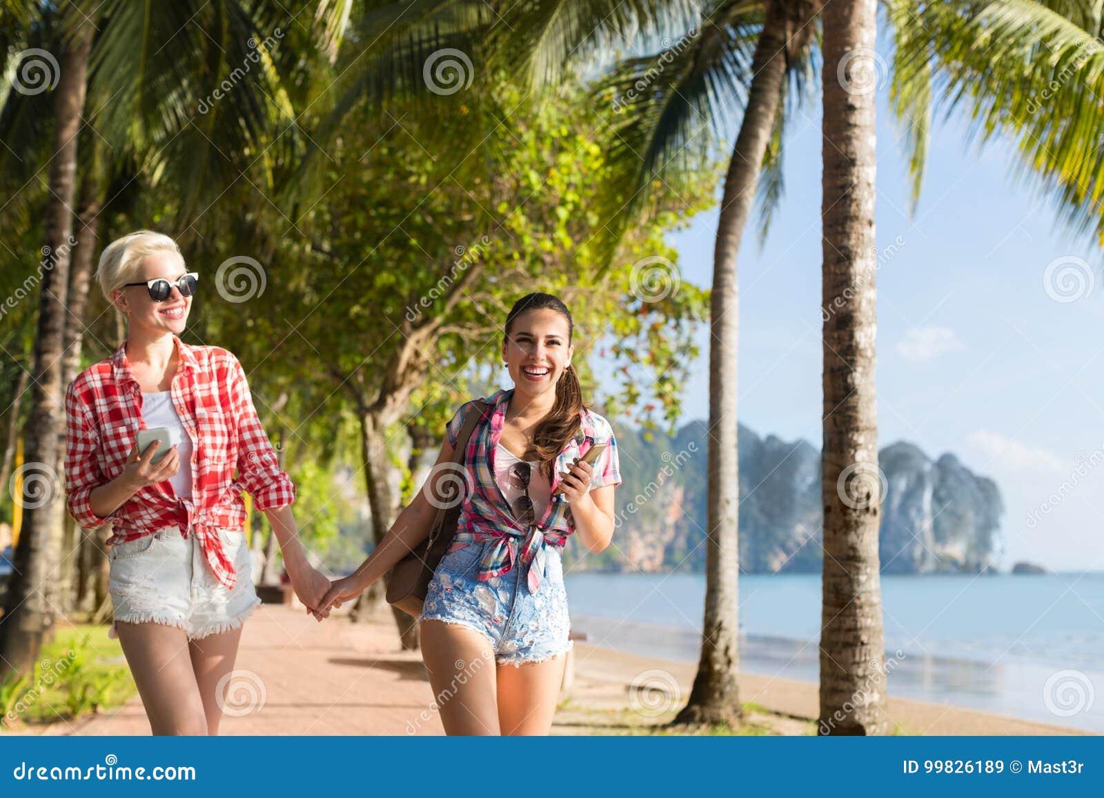 Δύο χέρια λαβής γυναικών που περπατούν στο τροπικό πάρκο φοινίκων στην παραλία, όμορφο νέο θηλυκό ζεύγος στις θερινές διακοπές