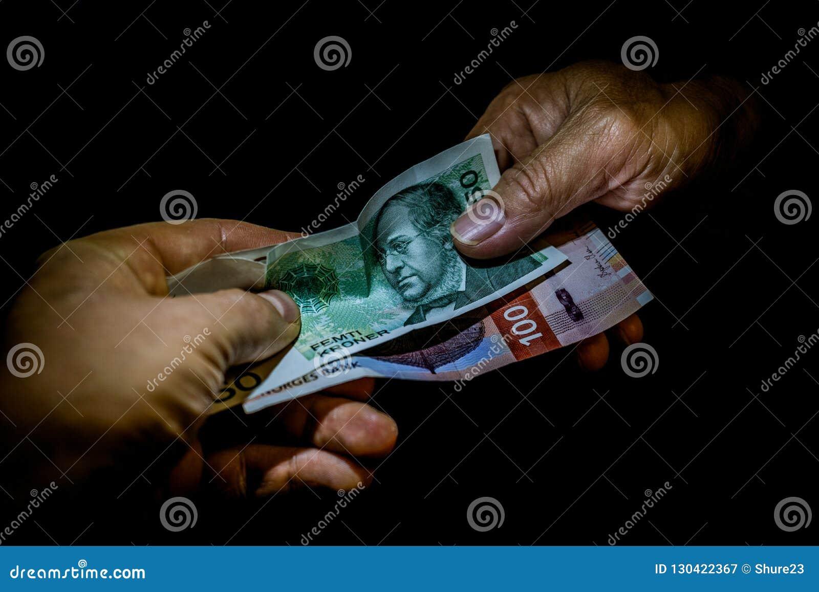 Δύο χέρια που παραδίδουν τα νορβηγικά τραπεζογραμμάτια κορωνών ο ένας στον άλλο