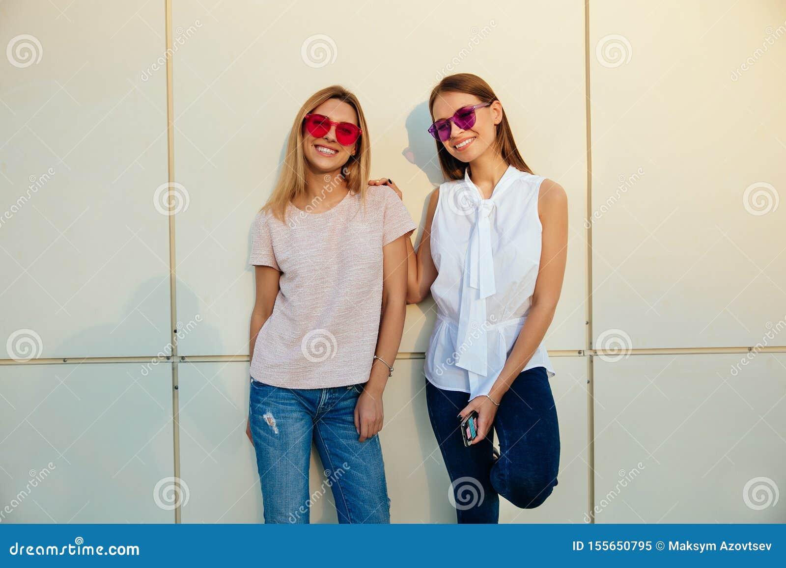 Δύο χαμογελώντας κορίτσια που θέτουν στη κάμερα, υπαίθρια