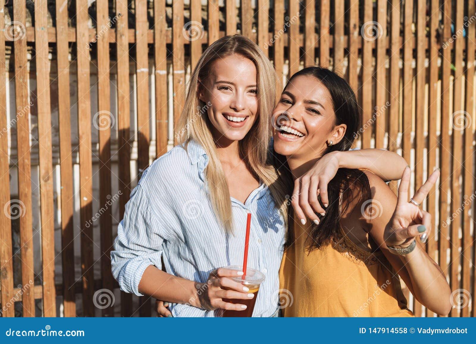 Δύο χαμογελώντας νέα κορίτσια που γελούν στεμένος υπαίθρια