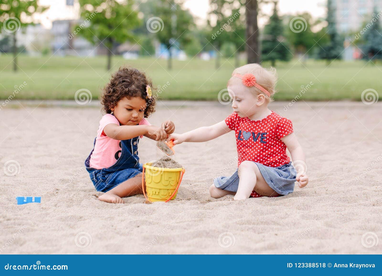 Δύο χαριτωμένα καυκάσια και ισπανικά λατινικά παιδιά μωρών μικρών παιδιών που κάθονται στο παιχνίδι Sandbox με τα πλαστικά ζωηρόχ