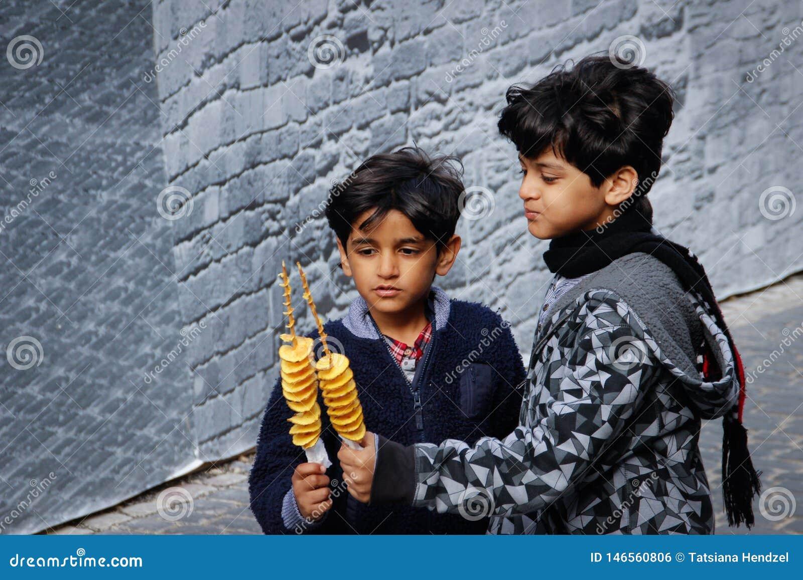Δύο χαριτωμένα μαύρος-μαλλιαρά μελαμψά του Αζερμπαϊτζάν αγόρια που παίζουν, που χαμογελούν και που τρώνε τα τσιπ σε ένα ραβδί