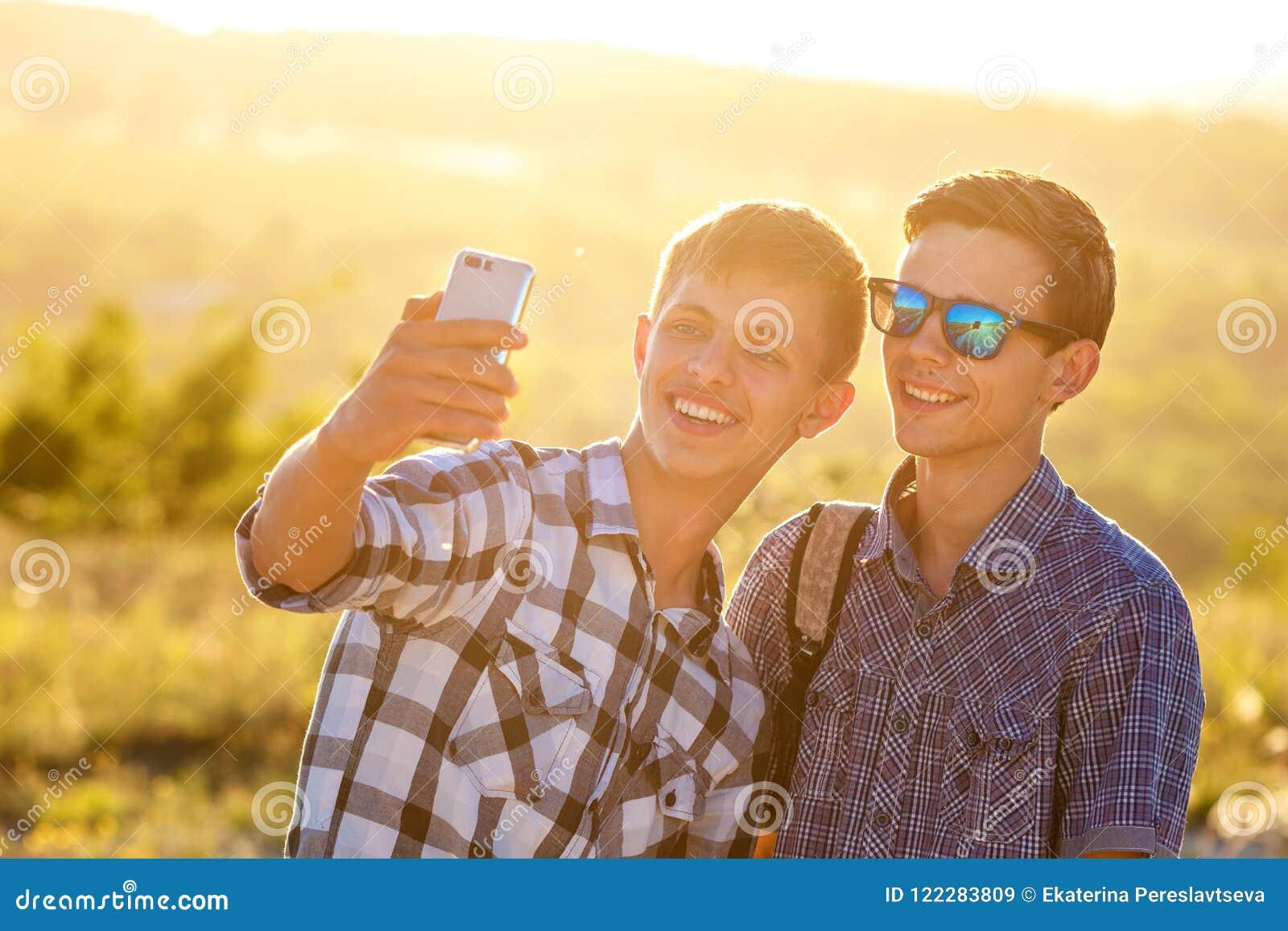 Δύο χαριτωμένοι τύποι παίρνουν selfies τους ευτυχείς φίλους φωτογραφίζονται στο τηλέφωνο