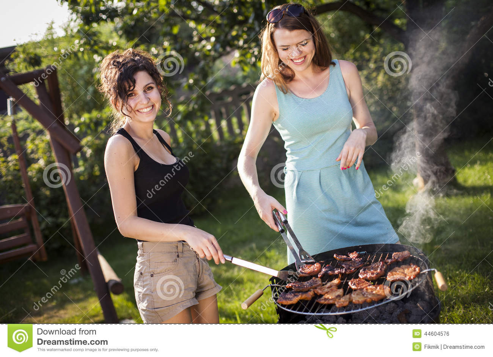Δύο όμορφα κορίτσια που κατασκευάζουν τα τρόφιμα στη σχάρα