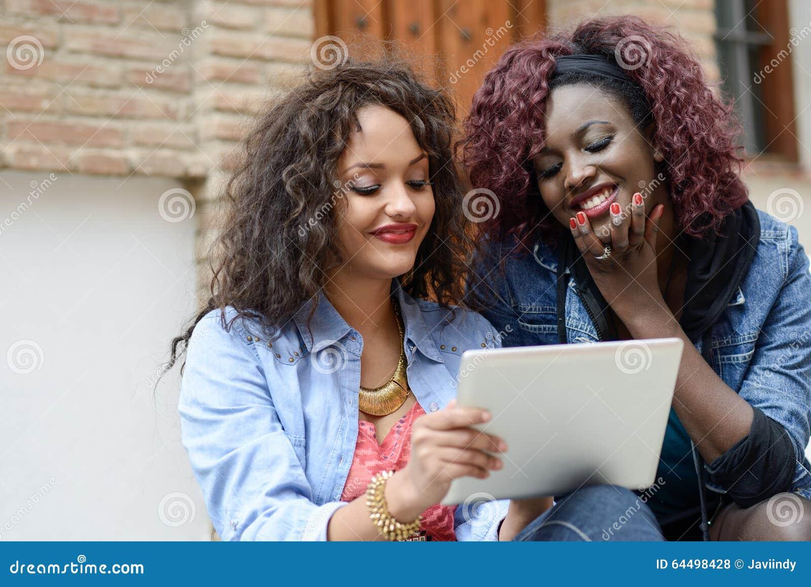 Δύο όμορφα μαύρα κορίτσια με τον υπολογιστή ταμπλετών στο αστικό backgrun