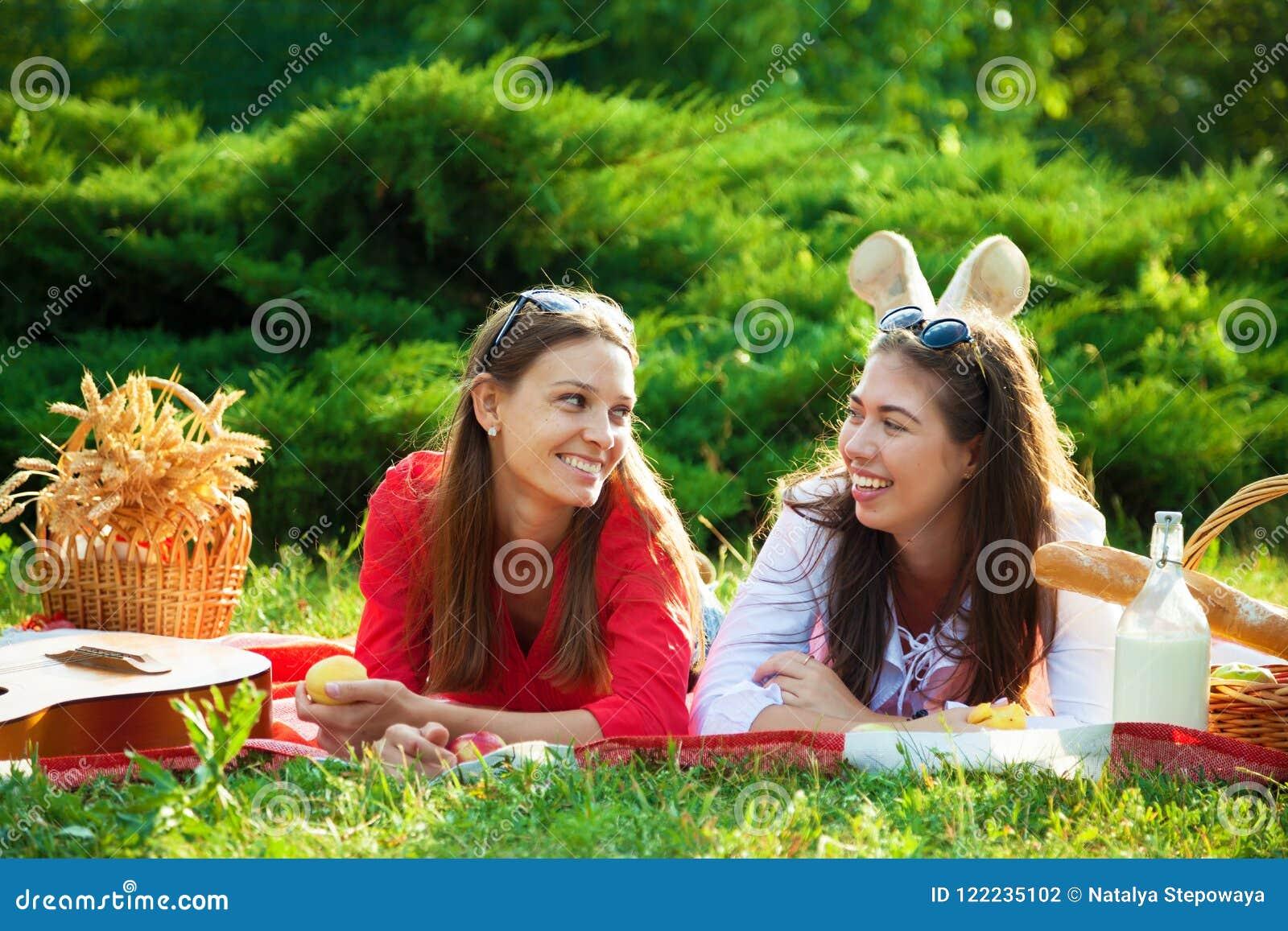 Δύο όμορφα νέα κορίτσια σε ένα πικ-νίκ το καλοκαίρι στο πάρκο που έχει τη διασκέδαση και που μιλά το διάστημα αντιγράφων