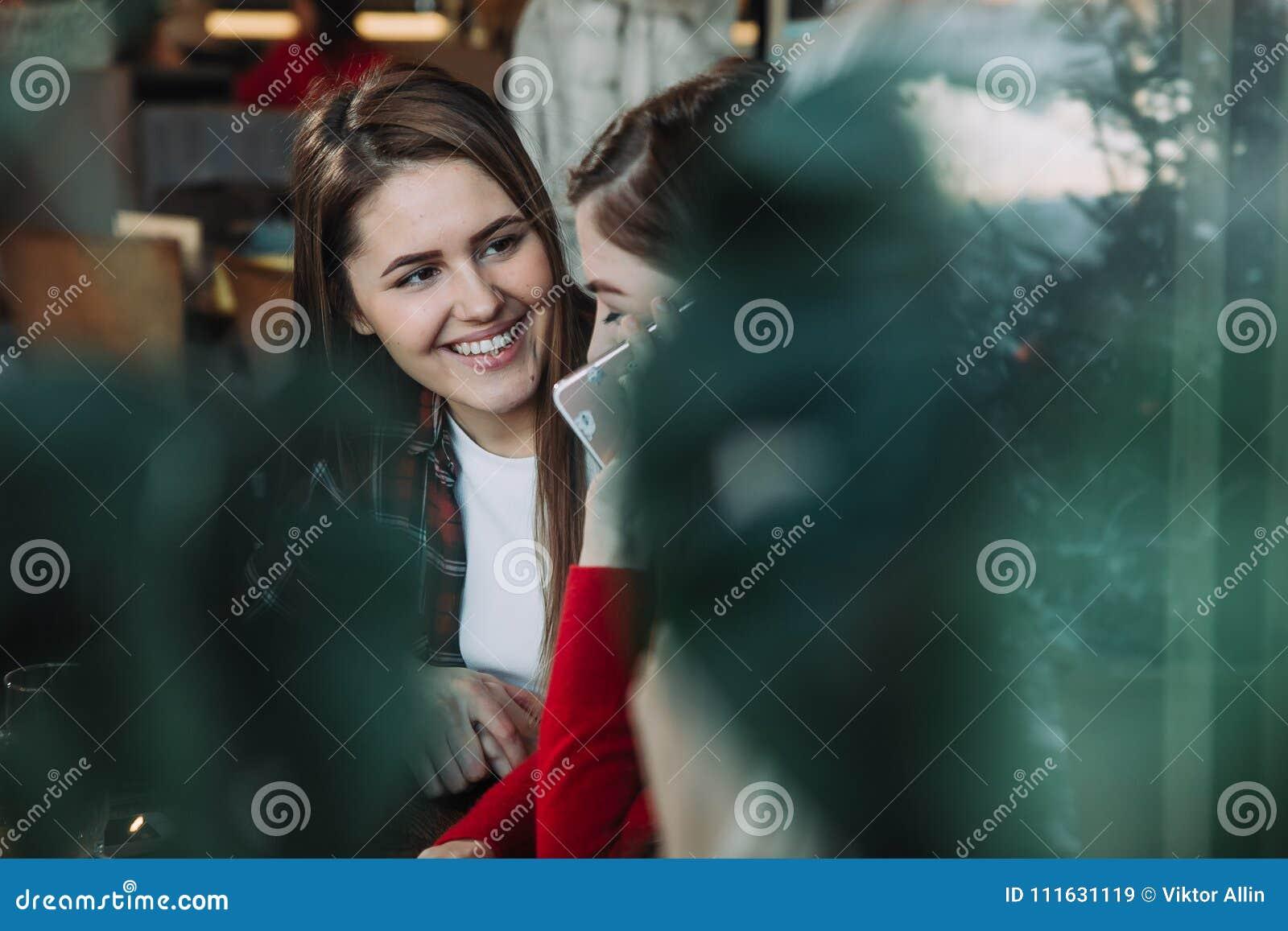 Δύο όμορφες γυναίκες που πίνουν τον καφέ και που κουβεντιάζουν στον καφέ