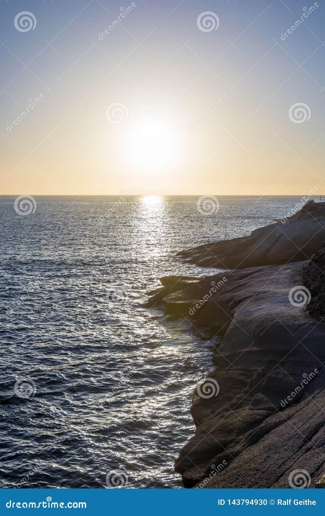 Δύσκολη ακτή με την ήρεμη θάλασσα και ένα ρομαντικό ηλιοβασίλεμα