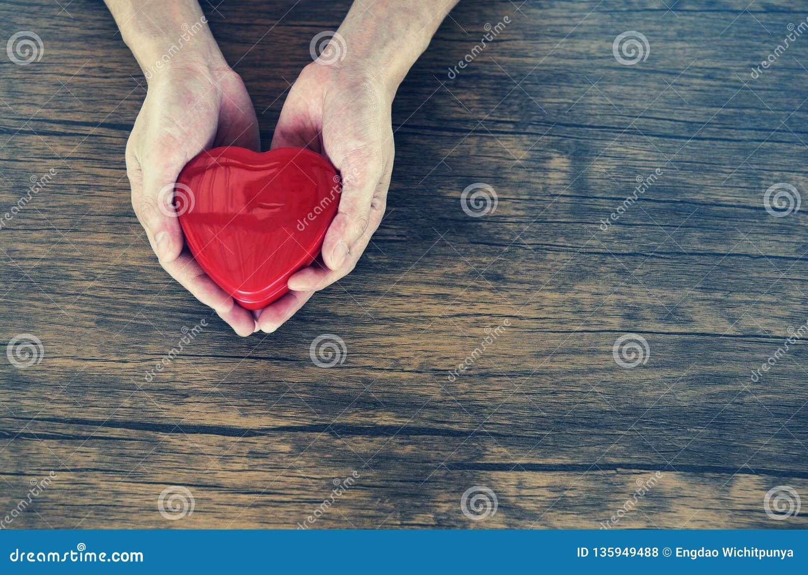 Δώστε το άτομο αγάπης που κρατά ότι η κόκκινη καρδιά στα χέρια για την ημέρα βαλεντίνων αγάπης δίνει τη βοήθεια δίνει τη ζεστασιά