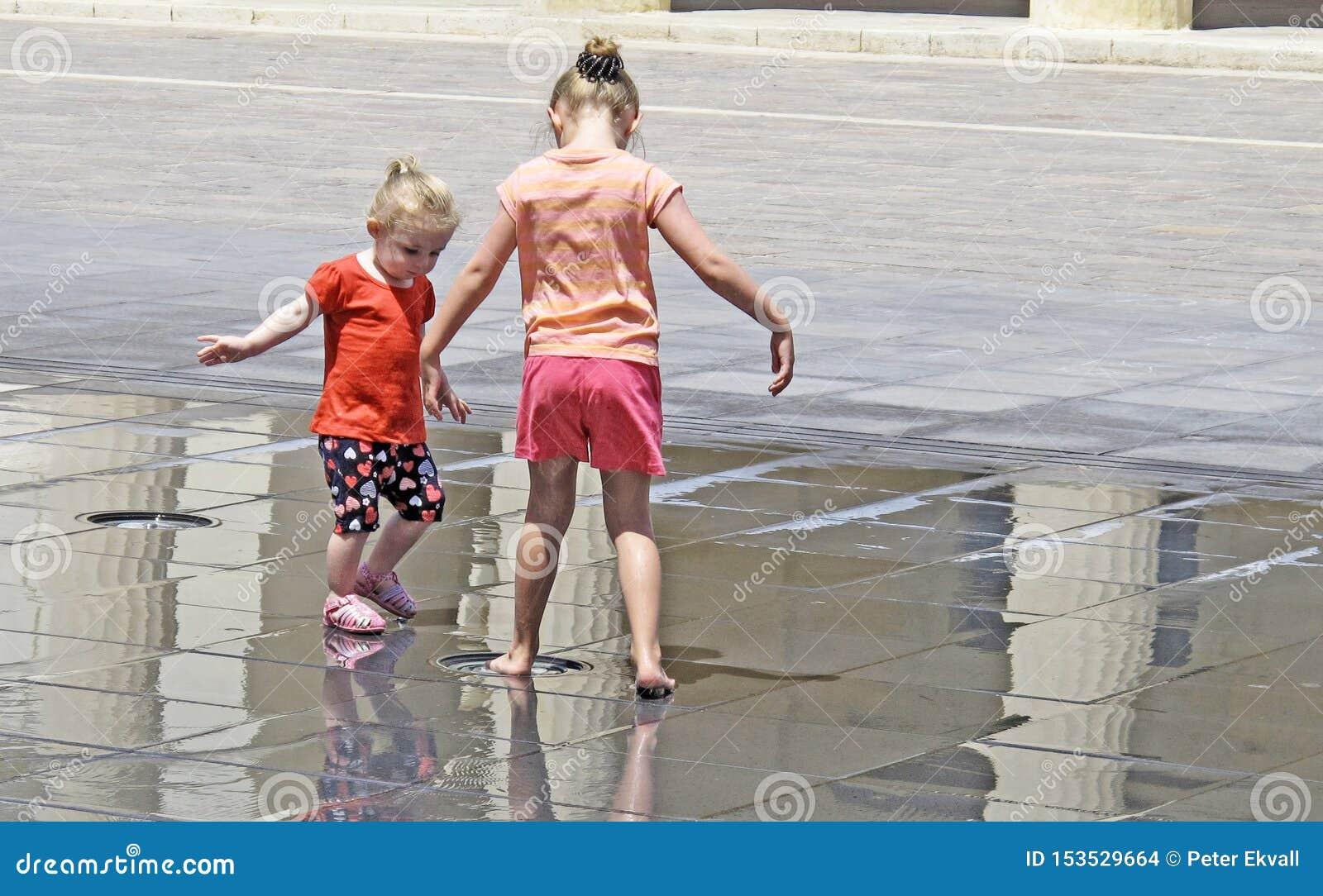 Είναι πολύ καυτό και δύο παιδιά που παίζουν στην πηγή στο τετράγωνο