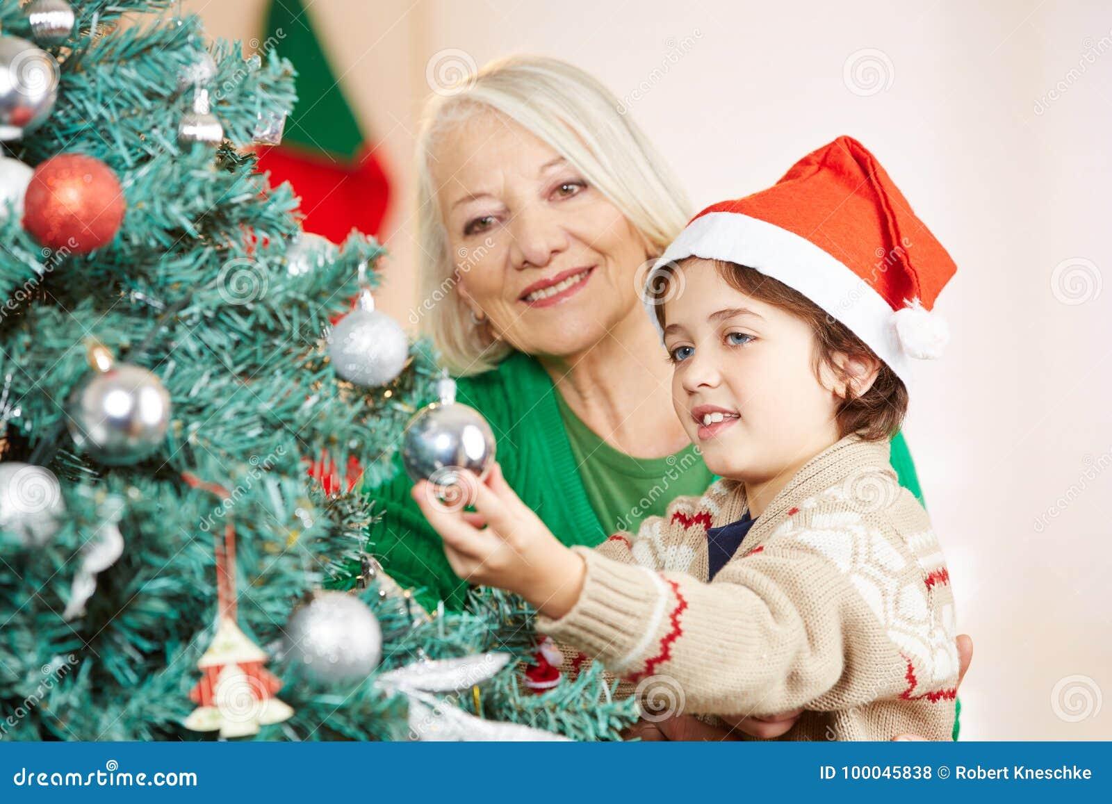 Εγγόνι που βοηθά τη γιαγιά για να διακοσμήσει το χριστουγεννιάτικο δέντρο