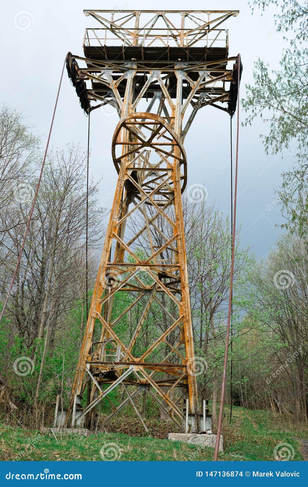 Εγκαταλειμμένος σκουριασμένος cable-way στυλοβάτης στο δάσος
