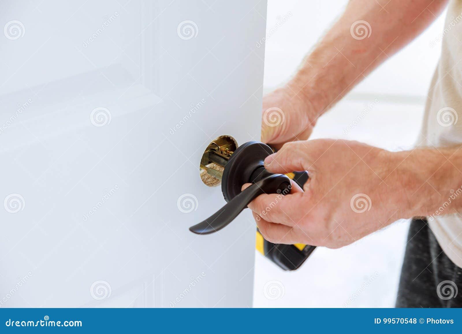 Εγκαταστήστε τη λαβή πορτών με μια κλειδαριά, ο ξυλουργός σφίγγει τη βίδα, χρησιμοποιώντας ένα ηλεκτρικό κατσαβίδι τρυπανιών