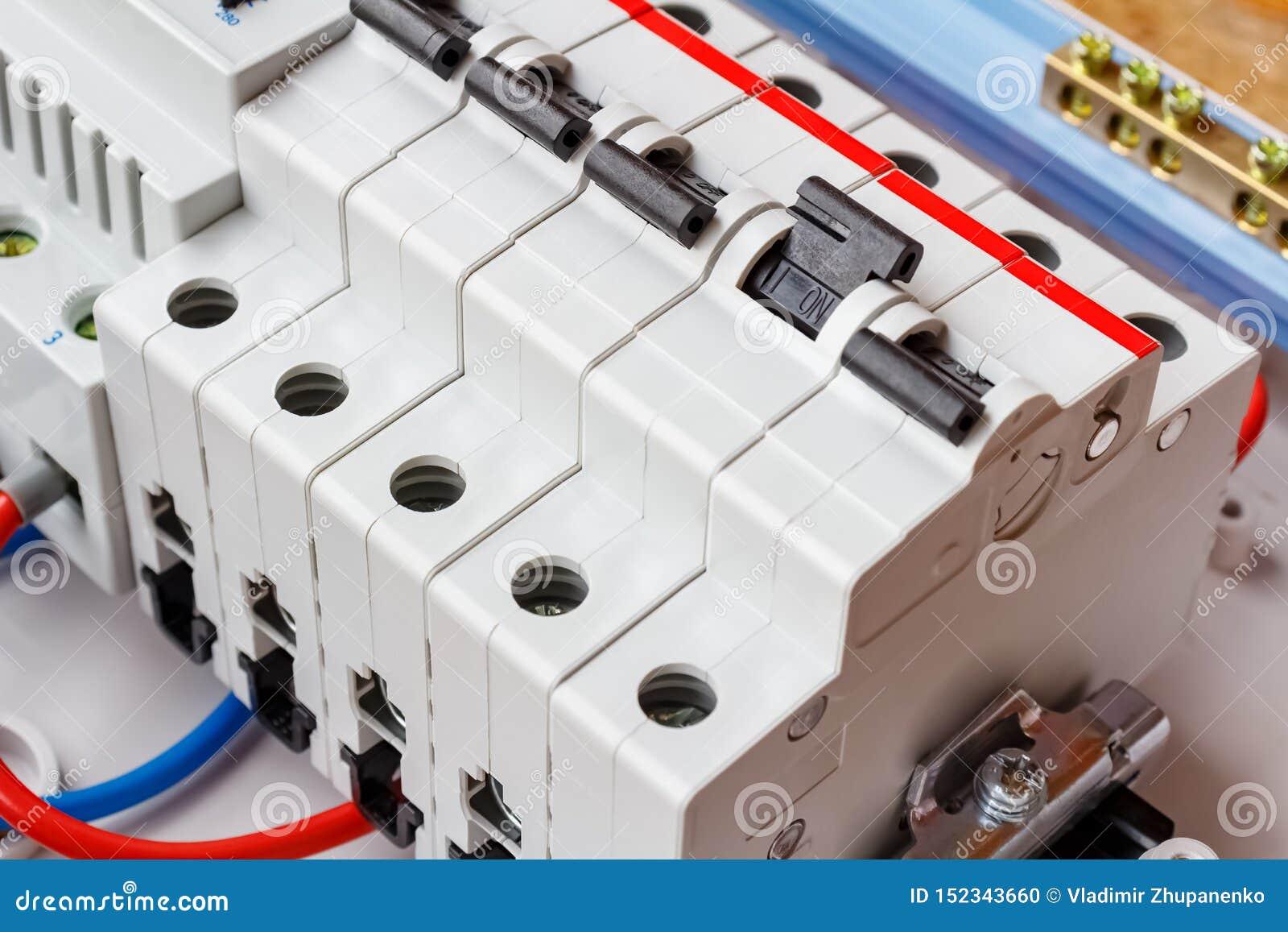 Εγκατεστημένοι αυτόματοι διακόπτες στη ράγα DIN στην άσπρη πλαστική να τοποθετήσει κινηματογράφηση σε πρώτο πλάνο κιβωτίων