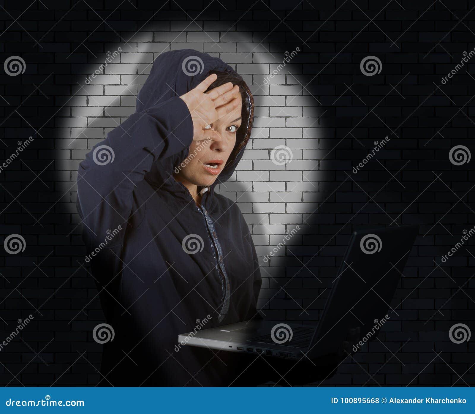 Εγκληματικός χάκερ γυναικών που φορά την κουκούλα στη χρησιμοποίηση ενός πνεύματος Catched lap-top