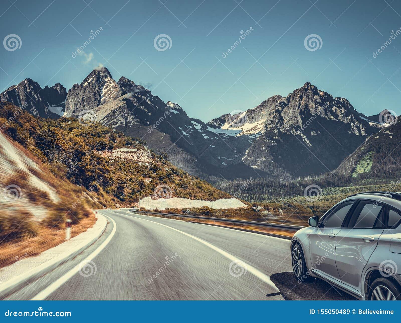Εθνική οδός μεταξύ του τοπίου βουνών Άσπρο αυτοκίνητο σε έναν δρόμο βουνών